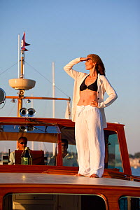 """Woman looking out to sea from deck of luxury motorboat """"Aphrodite"""". Newport, Rhode Island, USA, July 2010. Model and Property released.  -  Billy Black"""