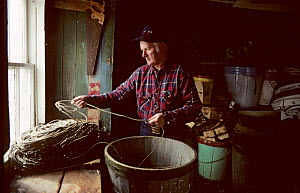 Man checking tub of longline fishing equipment. Francois, Newfoundland, Canada, 1992.  -  Bryan and Cherry Alexander