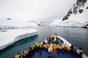 """Ice breaker """"Clipper Adventurer"""" passing an iceberg in the Lemaire Channel on a grey day, Antarctica, February 2009.  -  Bryan and Cherry Alexander"""