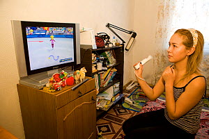 Young Chukchi woman playing Wii video game at her home in Anadyr. Chukotka, Siberia, Russia,  2010  -  Bryan and Cherry Alexander