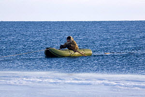 Yupik Eskimo hunter using inflatable boat to retrieve seals they have shot in Tkachen Bay. Chukotskiy Peninsula, Chukotka, Siberia, Russia, 2010 - Bryan and Cherry Alexander