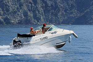 Couple in speedboat heading along Cote d'Azur past sea cliffs. France, May 2010. - Nick Upton