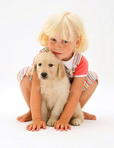 Portrait of young blonde haired girl sitting with Golden Retriever puppy. Model released - Jane Burton