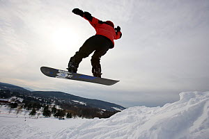 Snowboarder leaping into the air, Quechee Ski Hill, Quechee, Vermont, USA. February 2007 - Jerry Monkman