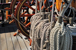"Steering wheel and ropes coiled around belaying pins aboard the ""Grand Turk / Etoile du Roy"", a three-masted sixth-rate frigate built in 1996 as a replica of HMS Blandford, built in 1741, Saint Malo,... - Philippe Clement"