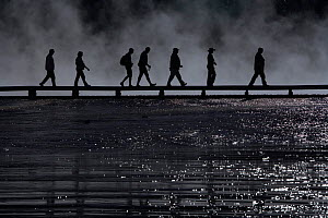 Tourists silhouetted on boardwalk at Midway Geyser Basin. Yellowstone National Park, Wyoming, USA, September.  -  Peter Cairns