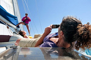 Woman taking photographs , on a sailing ship, with friends, National Park of the Tuscany archipelago, Italy, May 2010. Model released  -  Angelo Gandolfi