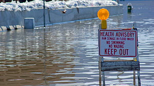 A sign warns of raw sewage in floodwater during the historic 2008 flood on the Mississippi River in Burlington, Iowa, USA, June 2008  -  Visuals Unlimited