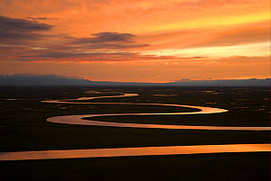 "Sunset over winding river in Bayinbuluke Swan Lake Nature Reserve. Xinjiang, China. Picture taken during filming of BBC ""Wild China"" TV Series, June 2006.  -  Barrie Britton"