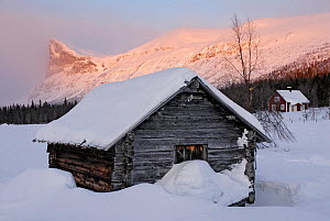 Traditional wooden farm hut beside Lake Laitaure, with Skierfe mountain in the background, Aktse, Laponia, Sweden, sunrise, winter  -  Orsolya Haarberg