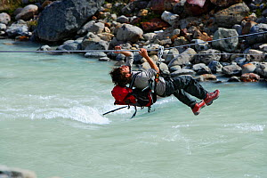 Alpinist mountaineer crossing the Fitz Roy river with a tyrolean crossing (also called zip-line, flying fox, zip wire, aerial runway, death slide), Los Glaciares National Park, Patagonia, Argentina, J...  -  Oriol Alamany