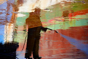 Reflection in water of worker in the boatyard at Guilvinec. Finistere, Brittany, France, October 2010.  -  Benoit Stichelbaut