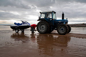 Jetski being unhitched from tractor ready for launching from a beach, Wales, March 2010. - Toby Roxburgh