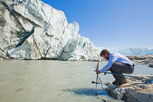 Dr. Ian Bartholomew using equipment to study melt water as part of a study to measure the speed of the receding Russell Glacier near Kangerlussuag, Greenland. July 2008  -  Visuals Unlimited
