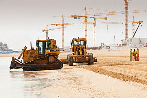Workers creating a new beach resort on former sea bed land in Dubai. March 2009 - Visuals Unlimited