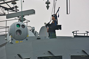 "Piper playing as ""HMS Campbeltown"" arrives in Liverpool for final visit prior to decommissioning. River Mersey, England, March 2011. For editorial use only. - Graham Brazendale"