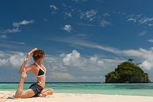 Young woman in a yoga pose on a sandy beach. Daram Island, Raja Ampat, West Papua, Indonesia, January 2010.  -  Juergen Freund