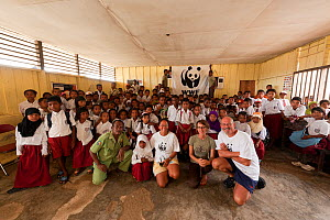 Students from Yellu Village posing with photographers Jurgen and Stella Freund  and Misool Eco Resort staff in front of the WWF panda flag. Misool, Raja Ampat, West Papua, Indonesia, January 2010.  -  Jurgen Freund