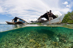 West Papuan fishermen in their outrigger houseboat over the shallow reef. North Raja Ampat, West Papua, Indonesia, February 2010  -  Jurgen Freund