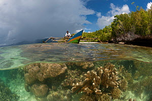 Split-level shot of a shallow coral reef with local West Papuan man in his dugout canoe. North Raja Ampat, West Papua, Indonesia, February 2010. - Jurgen Freund