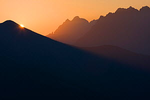 Sun rises behind Mt. Krisna in the Western Tatras, with the High Tatras in the background. Slovakia, August.  -  Bruno D'Amicis