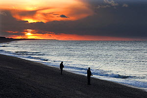 Silhouette of two men fishing from beach at  sunset, Weybourne, Norfolk, UK  -  Ernie Janes