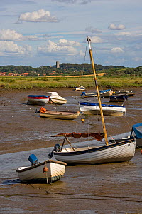 Boats stranded at low tide on the saltmarshes, Morston Quay, Norfolk, UK, with Blakeney Village in the background - Ernie Janes