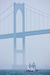 Two tiny boats in the mist beneath bridge during the Optimist North Americans, Newport, Rhode Island, USA, August 2010.  -  Onne van der Wal
