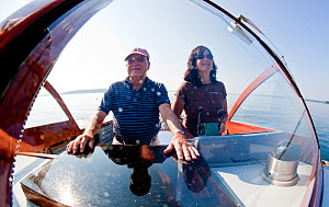 Couple in the cockpit of classic wooden power boat, Northeast Harbor, Maine, USA, September 2010. All non-editorial uses must be cleared individually. - Onne van der Wal