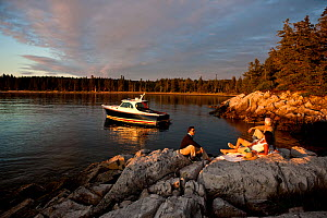 Hinckley T38 speedboat moored off Rhode Island, with people relaxing on rocks in foreground, USA, August 2008. Model and property released.  -  Onne van der Wal