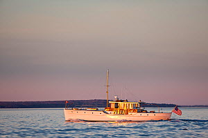 "Restored classic powerboat ""Carina"" in evening light off the coast of Newport, Rhode Island, USA, November 2010. All non-editorial uses must be cleared individually.  -  Onne van der Wal"