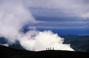 Hikers walk along the rim of Viti Crater, Iceland.  -  Visuals Unlimited