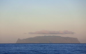 Inaccessible Island on the horizon topped with clouds. UNESCO World Heritage site and part of the Tristan da Cunha Group of South Atlantic Islands, March 2007. - Troels Jacobsen/Arcticphoto