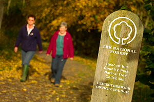 two women walking down woodland path with National Forest sign in foreground, The National Forest, Leicestershire, UK, November 2010 - Ben Hall / 2020VISION