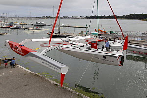 """Crane lowering MOD70 trimaran """"Veolia Environnement"""" into the water. Lorient, France, June 2011. All non-editorial uses must be cleared individually.  -  Benoit Stichelbaut"""
