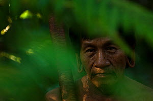 A Huaorani man seen through leaves in the forest undergrowth. Gabaro Community, Yasuni National Park, Ecuador, June 2007. Model release #GA21.  -  Pete Oxford