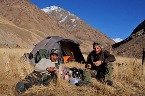 Photographer Eric Dragesco and guide resting outside their tent, on expedition to find Tien Shan Argali (Ovis ammon karelini). Naryn National Park, Kyrgyzstan, Central Asia, November.  -  Eric Dragesco