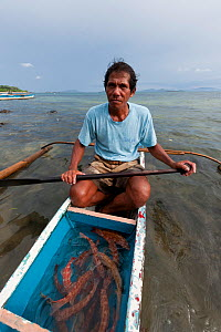 Hook and line fisherman with his day's catch of a dozen live Coral trout (Plectropomus leopardus) to sell to a Live Reef Fish grower, Palawan, Philippines, May 2009. - Jurgen Freund