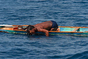Hook and line fishermen in his dugout canoe wearing self-made goggles to target the fish that he aims to catch, Indonesia, November 2009. - Jurgen Freund