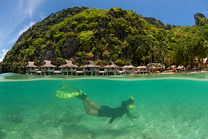 Snorkeler swimming underwater, split level, with Miniloc Island Resort in the background, El Nido, Palawan, Philippines, May 2009. Model released  -  Jurgen Freund