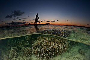 Split level image of Papuan fisherman standing on his dugout canoe over shallow corals, New Ireland, Papua New Guinea, June 2010  -  Jurgen Freund