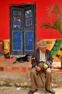An old man and a dog sitting on the street in the colourful city of Ro�quira ('City of Pots'). Boyaca department, Colombia, February 2011.  -  Luiz Claudio Marigo
