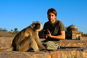 Photographer Axel Gomille sitting by a Southern plains grey / Hanuman langur {Semnopithecus dussumieri} Ranthambhore Fort, Rajasthan, India  -  Axel Gomille