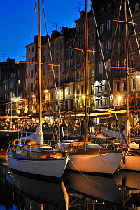 Sailing boats and tourists at pavement cafes / sidewalk cafes along the quay of the Honfleur harbour at night. Normandy, France, October 2010.  -  Philippe Clement