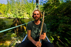 A man sitting in the cable car of a chair bridge as it crosses a river. The West Coast Trail, Pacific Rim National Park, Vancouver Island, Canada, September 2010. Model released - Matthew Maran
