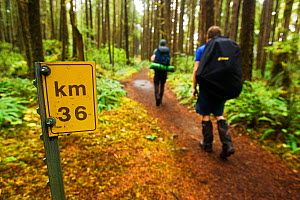 Hikers passing a sign informing them that they either have 36km to go, or have come 36km. The West Coast Trail, Pacific Rim National Park, Vancouver Island, Canada, September. Models released. - Matthew Maran