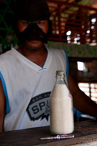 Man preparing a homemade explosive for fishing. The bomb is made by filling a glass bottle with potassium or ammonium nitrate, kerosine and rocks. It is thrown onto a reef with schooling fish and indi...  -  Juergen Freund