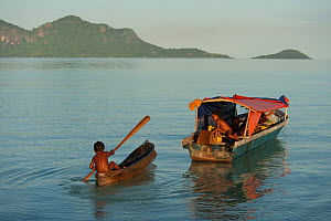 Child in canoe beside traditional fishing boat, Semporna, Sabah, Borneo, Malaysia, June 2009.  -  Jurgen Freund