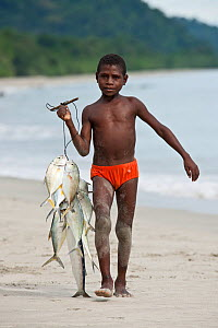 Young West Papuan boys carrying a catch of fresh fish to the kitchen. Batu Rumah, Bird's Head Peninsula, West Papua, Indonesia, July 2009.  -  Jurgen Freund