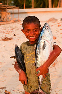 Young Indonesian boy posing with two freshly-caught fish. Kei Islands, Moluccas, Indonesia, November 2009.  -  Jurgen Freund
